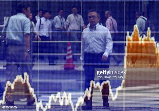 Pedestrians are reflected on a share prices board in Tokyo on June 22 2015 Japan's share prices rose 16107 points to close at 2033531 points at the...
