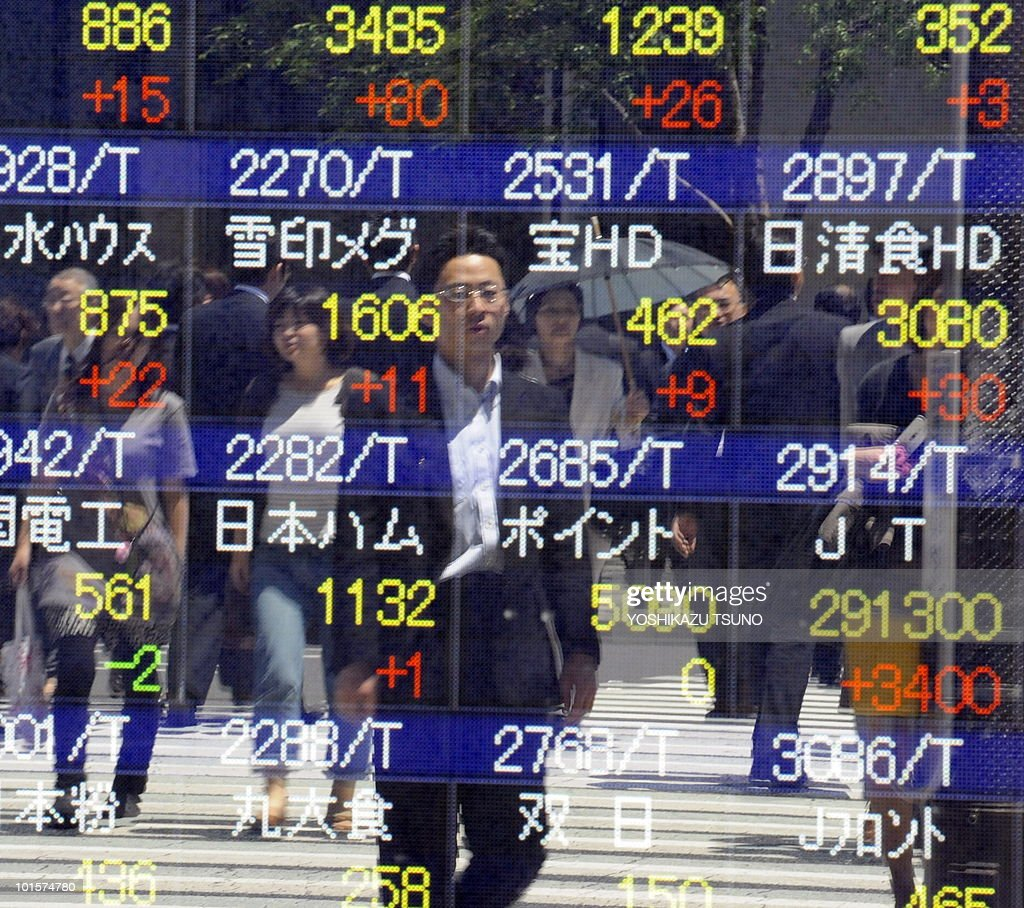 Pedestrians are reflected on a share prices board in Tokyo on June 3, 2010. Tokyo shares jumped more than three percent helped by a Wall Street surge and weaker yen amid growing expectations Finance Minister Naoto Kan will become Japan's next premier, brokers said. AFP PHOTO / Yoshikazu TSUNO