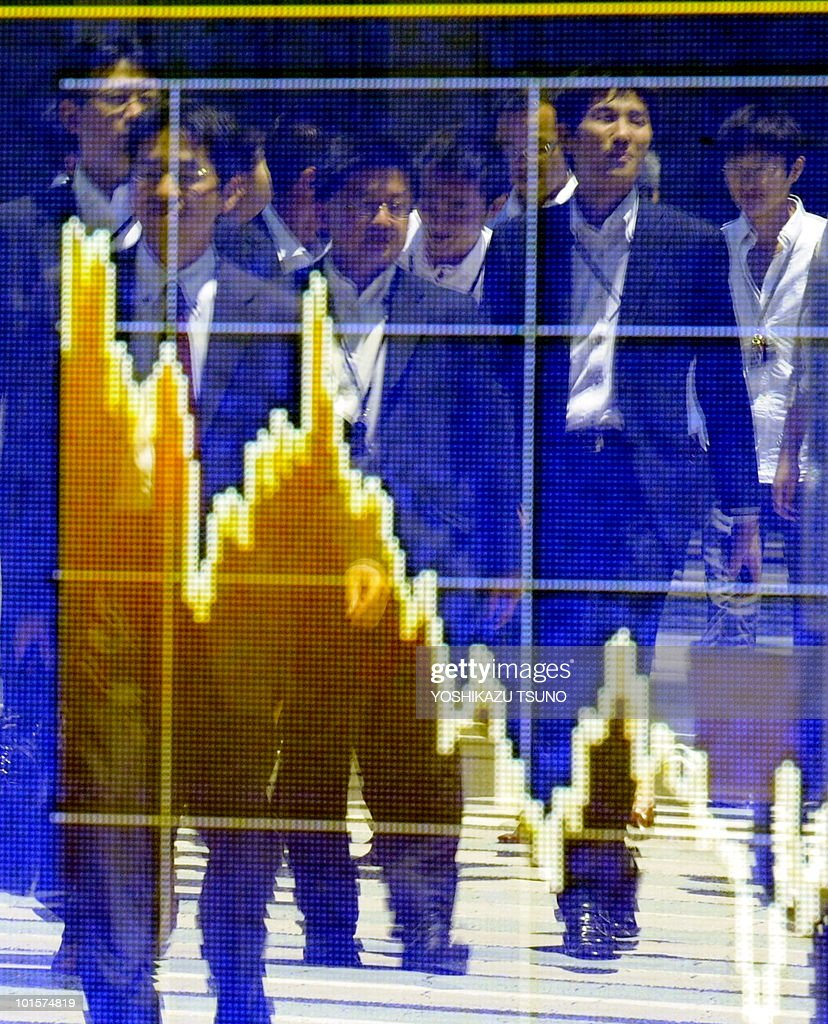 Pedestrians are reflected on a share prices board in Tokyo on June 3, 2010. Tokyo shares jumped more than three percent, ending the morning session 252.14 points up at 9,855.38, helped by a Wall Street surge and weaker yen amid growing expectations Finance Minister Naoto Kan will become Japan's next premier, brokers said. The headline Nikkei index closed up 297.41 points, a rise of 3.10 percent. AFP PHOTO / Yoshikazu TSUNO
