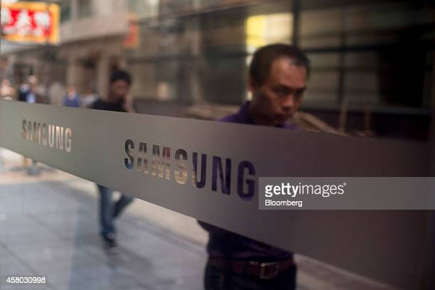 Pedestrians are reflected on a window displaying Samsung Electronics Co logos outside a Samsung Partnershop retail store in the Central district of...