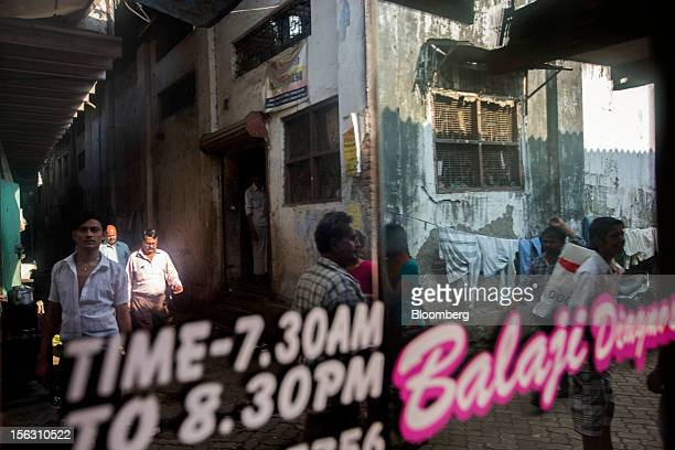 Pedestrians are reflected on a window in the Dharavi slum area of Mumbai India on Friday Nov 9 2012 Indian industrial production unexpectedly fell in...