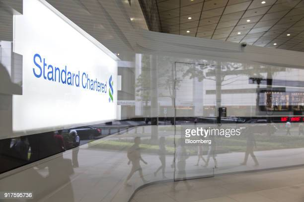 Pedestrians are reflected on a window of a Standard Chartered Plc bank branch in the central business district of Singapore on Monday Feb 12 2018...