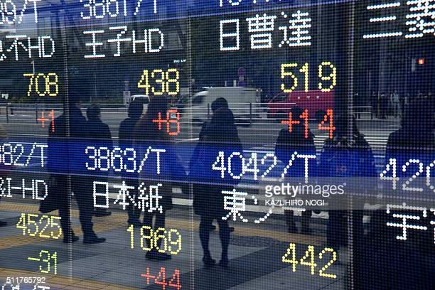 Pedestrians are reflected on an electric quotation board showing numbers of the Tokyo Stock Exchange in front of a securities company in Tokyo on...