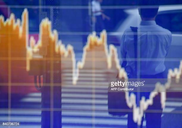 Pedestrians are reflected on an electronic stock indicator at the window of a securities company in Tokyo on August 30 2017 The benchmark Nikkei 225...