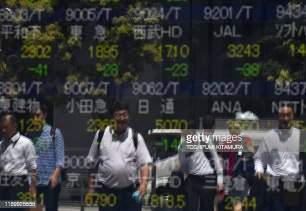 Pedestrians are reflected on an electronics stock indicator at the window of a securities company in Tokyo on August 6 2019 Tokyo stocks opened down...
