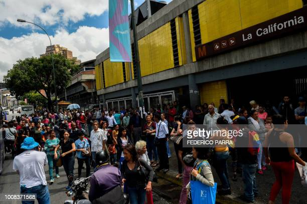 Pedestrians are seen on a packed street in Caracas during a partial power cut on July 31 2018 A power failure cut electricity to 80 percent of the...