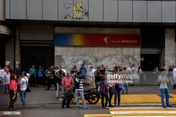 Pedestrians are seen on a street in Caracas during a partial power cut on July 31 2018 A power failure cut electricity to 80 percent of the...