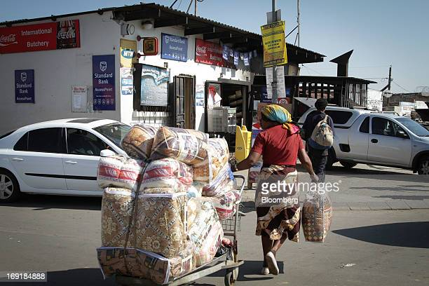 Pedestrians are seen outside a supermarket store advertising an access point for MPesa mobile phone money transfer services operated by Standard Bank...
