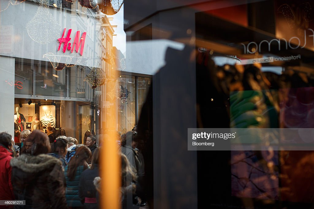Pedestrians are seen reflected in a store window as they pass a Hennes & Mauritz AB (H&M) fashion store in Amsterdam, Netherlands, on Thursday, Jan. 2, 2014. The Netherlands will grow by 0.5 percent in 2014 as the world economy improves and consumer confidence picks up, the country's central bank forecast Dec. 9. Photographer: Jasper Juinen/Bloomberg via Getty Images