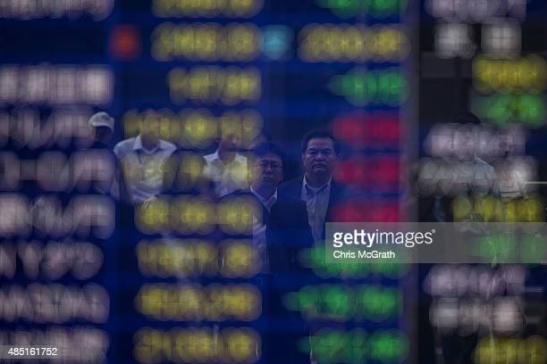 Pedestrians are seen reflected in an electronic screen showing global stock market information on the street in Tokyo on August 25 2015 Japan's share...