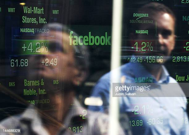 Pedestrians are seen reflected in the window of the Nasdaq studios as the Facebook logo is displayed on a ticker board on May 17 2012 in New York...