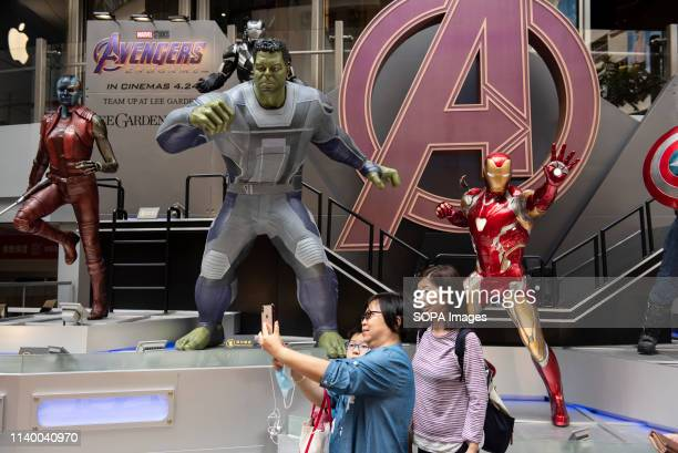 Pedestrians are seen taking a selfie with Marvel and Marvel Studios figures owned by Disney to commemorate and advertise the Avengers Endgame movie...