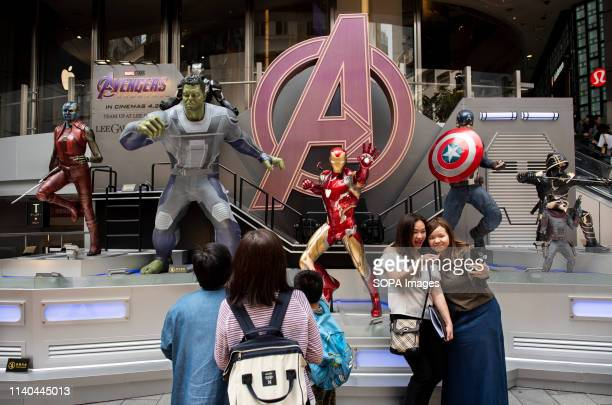 Pedestrians are seen taking a selfie with Marvel and Marvel Studios figures owned by Disney to commemorate and advertise of the Avengers Endgame...