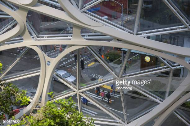 Pedestrians are seen through the glass of an Amazoncom Inc Sphere in Seattle Washington US on Tuesday Jan 23 2018 The online retailer is scheduled to...