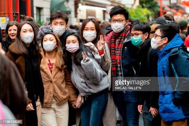 Pedestrians are seen wearing a surgical masks as they pose for a photograph in London's China Town on January 25 2020 European airports from London...