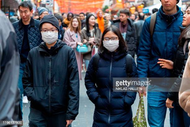 Pedestrians are seen wearing a surgical masks in London's China Town on January 25 2020 European airports from London to Moscow stepped up checks...