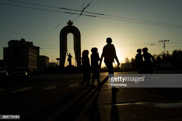 Pedestrians are silhouetted as they walk past the Statue of Ismoili Somoni in Dushanbe Tajikistan on Saturday April 21 2018 Flung into independence...