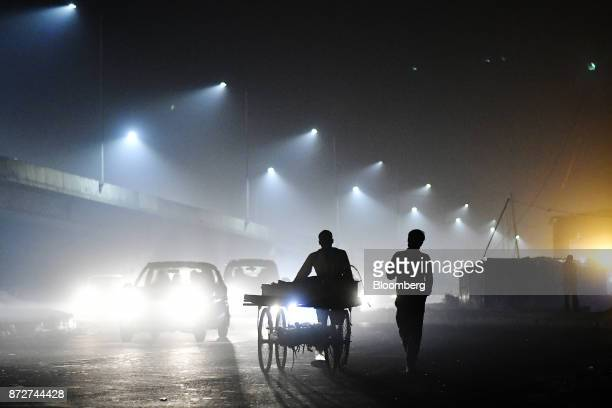 Pedestrians are silhouetted as traffic moves along a road shrouded in smog in New Delhi India on Friday Nov 10 2017 Thick toxic smog enveloped New...
