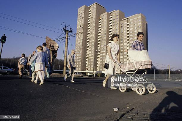 Pedestrians at the Leninplatz in Eastern Berlin In the background a block of flats