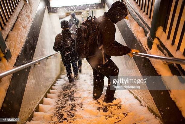 Pedestrians at the Morningside Heights campus of Columbia University walk down the steps to the subway during a snow storm on January 21, 2014 in New...