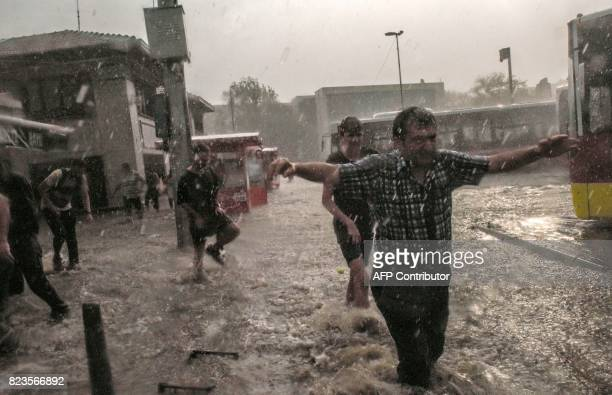TOPSHOT Pedestrians attempt to cross a street during a heavy downpour of rain and hail at Besiktas near Istanbul on July 27 2017 / AFP PHOTO / Bulent...