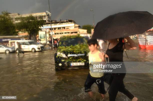 Pedestrians attempt to cross a street during a heavy downpour of rain and hail at Besiktas near Istanbul on July 27 2017 / AFP PHOTO / Bulent KILIC