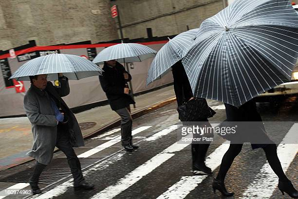 Pedestrians battle wind rain and sleet as Manhattan prepares for a major winter storm on February 8 2013 in New York City New York City and much of...