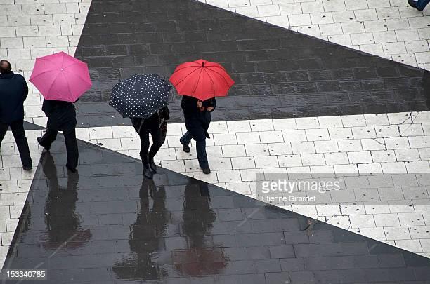 Pedestrians below with umbrellas