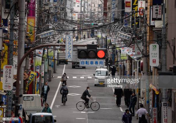 Pedestrians bicyclists and traffic pass under power lines in Hachioji City Tokyo Japan on Wednesday March 15 2017 The Tokyo government plans to start...