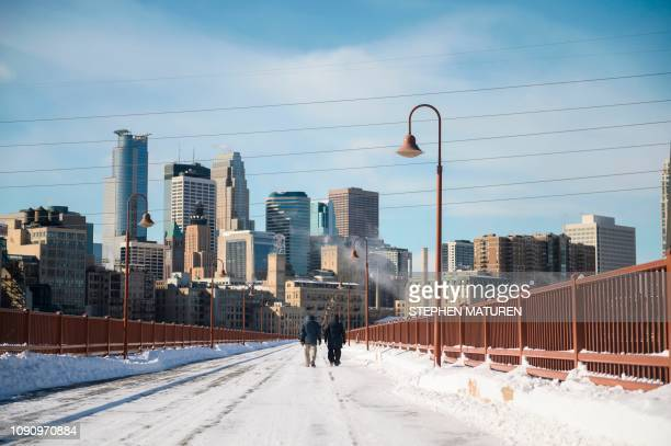 Pedestrians brave the cold to go for a walk on the Stone Arch Bridge on January 29, 2019 in Minneapolis, Minnesota. - The polar vortex is here --...