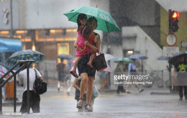 Pedestrians braving the heavy rain in Shek Kip Mei Under the influence of an active southwesterly airstream heavy showers and thunderstorms persisted...