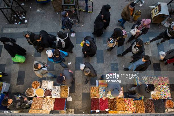 Pedestrians browse food stalls at a street market in Tehran Iran on Monday Jan 8 2018 A wave of bad loans from unregulated lenders has rocked the...