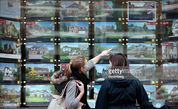 Pedestrians browse residential properties for sale in the window of an estate agent in Esher UK on Monday Nov 21 2011 UK home sellers cut asking...