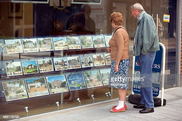 Pedestrians browse residential property advertisements in the window of a real estate agent in Woking Surrey UK on Monday Sept 14 2015 In a recent...