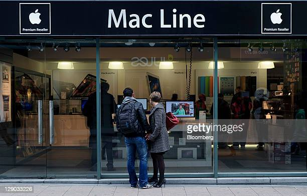 Pedestrians browse the window display of an Apple Inc computer reseller store in Brussels Belgium on Tuesday Oct 11 2011 Belgium's Prime Minister...