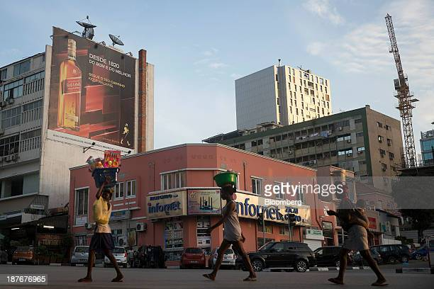 Pedestrians carry goods on their heads as they cross a road beneath a billboard advertising Johnnie Walker 'Red Label' whisky in Luanda Angola on...