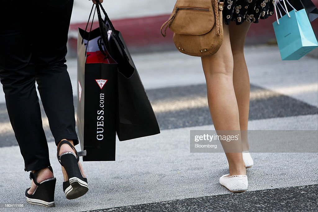 Pedestrians carry Guess? Inc. and Tiffany & Co. shopping bags on Rodeo Drive in Beverly Hills, California, U.S., on Wednesday, Sept. 11, 2013. The U.S. Census Bureau is scheduled to release retail sales figures on Sept. 13. Photographer: Patrick T. Fallon/Bloomberg via Getty Images