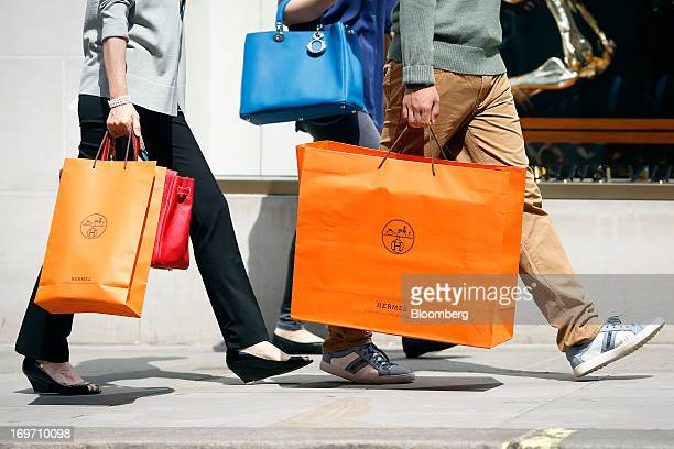 Pedestrians carry Hermes International SCA branded shopping bags as they walk along New Bond Street in London UK on Friday May 31 2013 LVMH Moet...