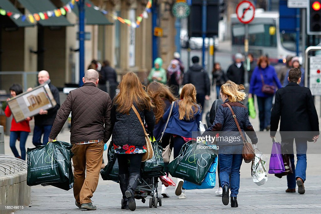 Pedestrians carry Marks & Spencer Group Plc (M&S)-branded shopping bags along a street in Manchester, U.K., on Monday, April 1, 2013. U.K. retail sales unexpectedly stagnated in March in a sign that consumer spending remains under pressure from higher energy bills and weak wage growth. Photographer: Paul Thomas/Bloomberg via Getty Images
