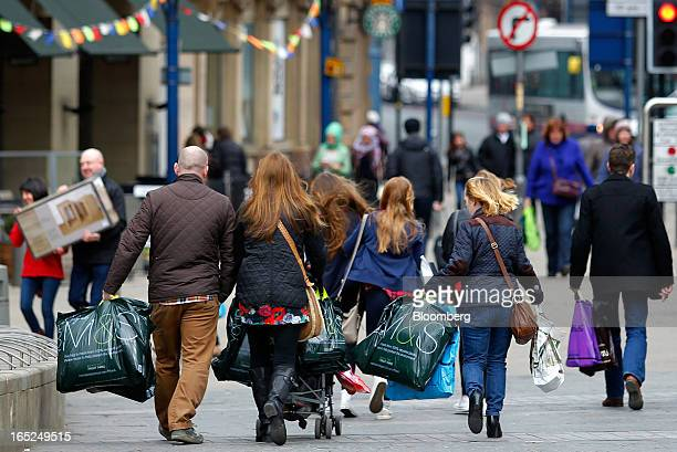 Pedestrians carry Marks Spencer Group Plc branded shopping bags along a street in Manchester UK on Monday April 1 2013 UK retail sales unexpectedly...