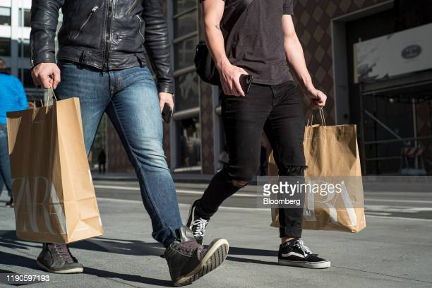Pedestrians carry shooting bags from Zara fashion store operated by Inditex SA in San Francisco California US on Thursday Dec 26 2019 Confidence...
