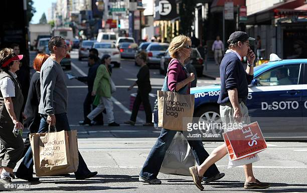 Pedestrians carry shopping bags as they walk through the Union Square shopping district October 1 2009 in San Francisco California The Commerce...