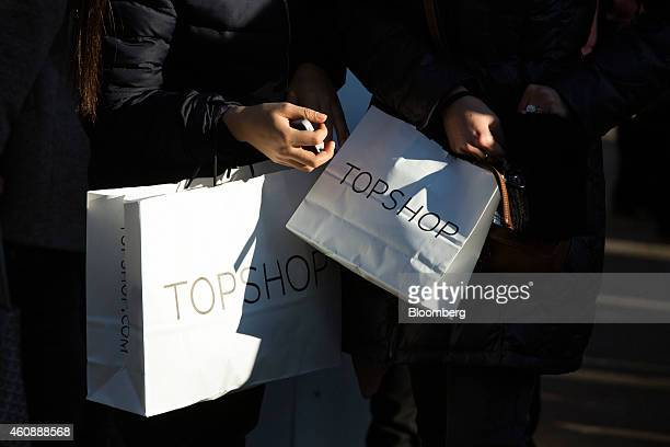 Pedestrians carry shopping bags from a Topshop store as they walk along Regents Street in London UK on Monday Dec 29 2014 The UK may overtake France...