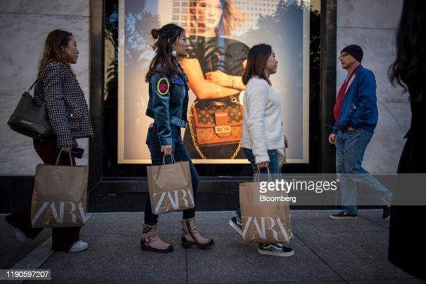 Pedestrians carry shopping bags from Zara fashion store operated by Inditex SA in San Francisco California US on Thursday Dec 26 2019 Confidence...