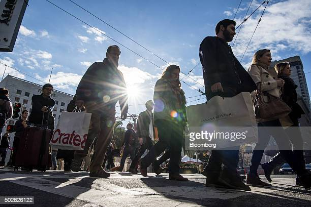 Pedestrians carry shopping bags through downtown San Francisco California US on Monday Dec 28 2015 A late surge in shopping and pentup demand for...