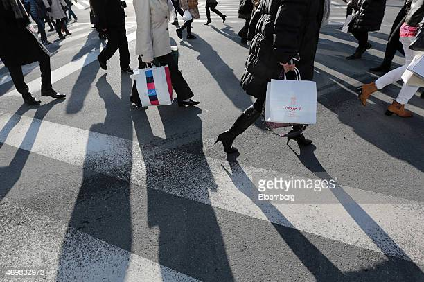 Pedestrians carry shopping bags while crossing an intersection in the Ginza district of Tokyo, Japan, on Sunday, Feb. 16, 2014. Japans economy grew...