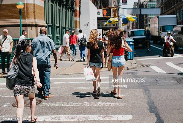 Pedestrians carry shopping bags while crossing the street in the SoHo neighborhood of New York US on Wednesday June 18 2014 The Bloomberg Consumer...
