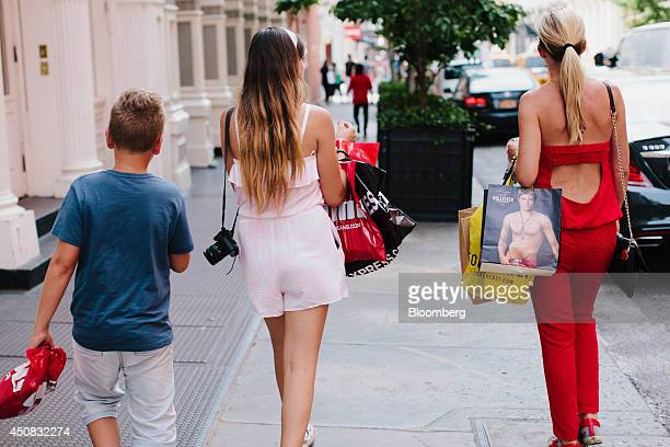 Pedestrians carry shopping bags while walking in the SoHo neighborhood of New York US on Wednesday June 18 2014 The Bloomberg Consumer Comfort Index...