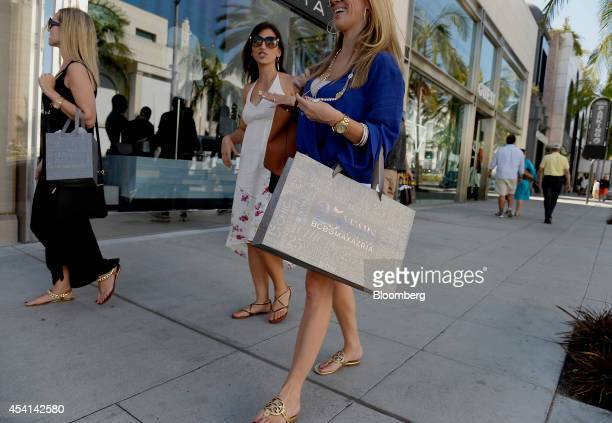 Pedestrians carry shopping bags while walking on Rodeo Drive in Beverly Hills California US on Friday Aug 22 2014 The Conference Board is scheduled...