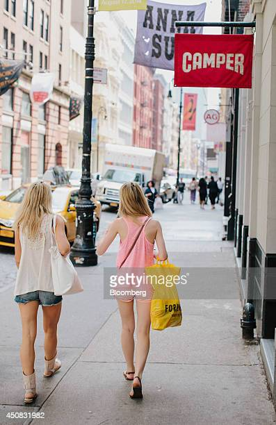 Pedestrians carry shopping bags while walking past the Camper store in the SoHo neighborhood of New York US on Wednesday June 18 2014 The Bloomberg...